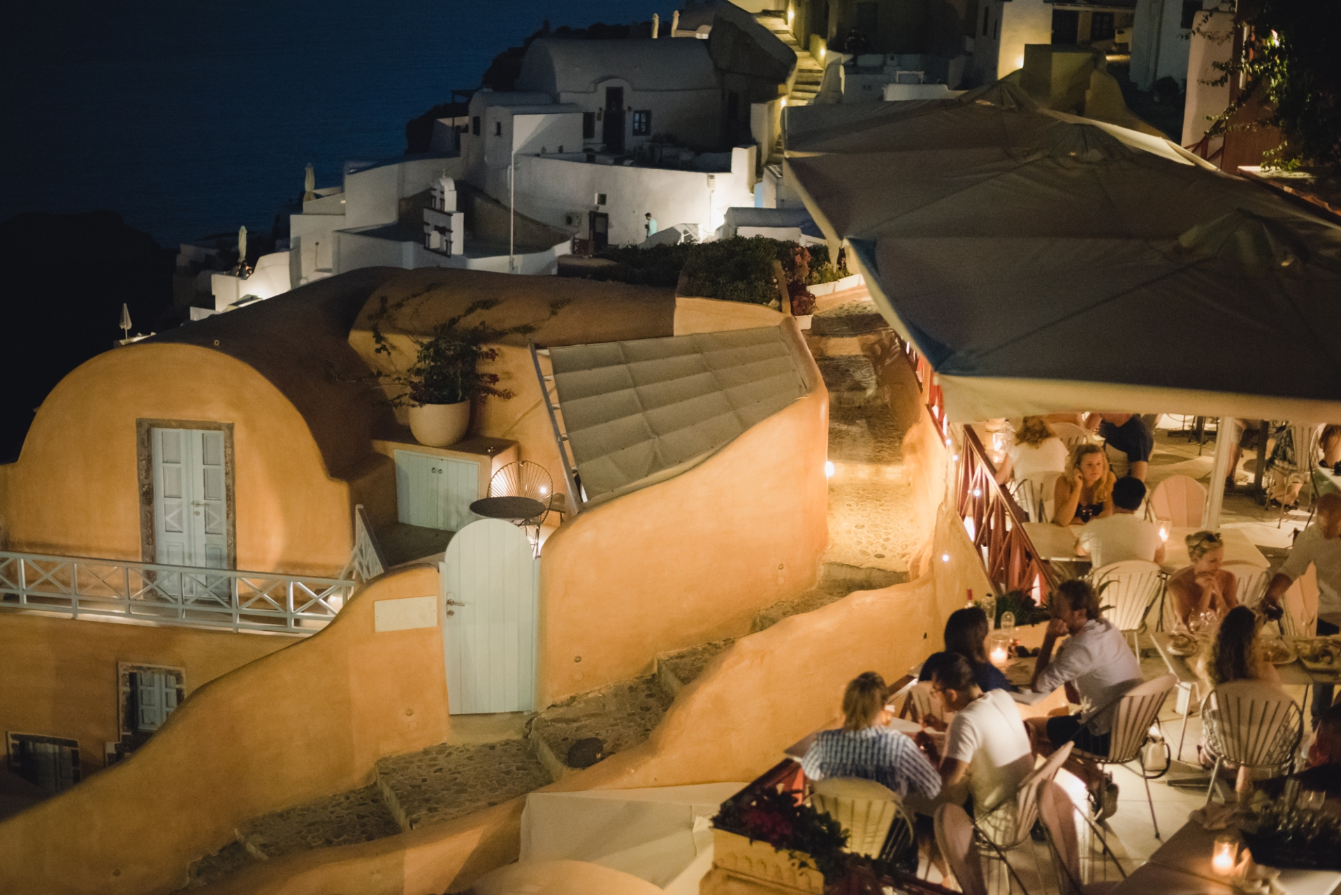 Restaurant in Santorini, Oia. People enjoining their meal at twilight.