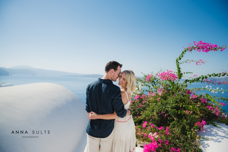 Australian couple hugging in Greece, next to Santorini flowers