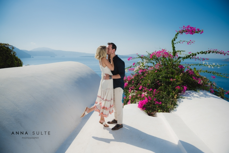 Australian couple holding hands in Greece, next to Santorini flowers