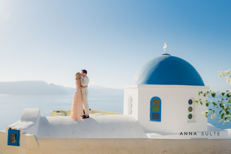 Couple on the rooftop in Santorini, blue church