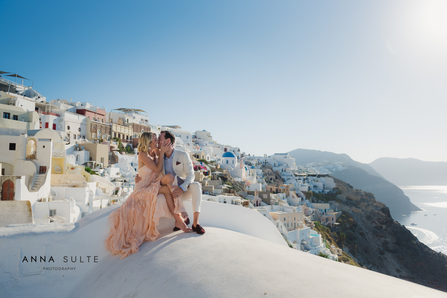 Couple sitting, iconic Greek view behind them