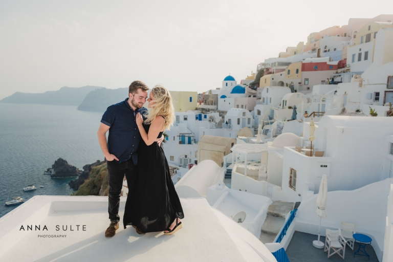 Girl in a black dress hugs her husband on a balcony with Santorini view