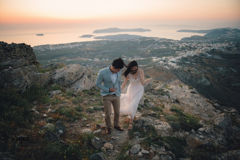 Married couple walk on the mountain at sunset