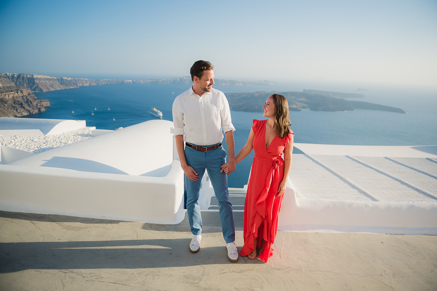 Couple holding hands by the Santorini view. Volcano , white washed houses and steps.