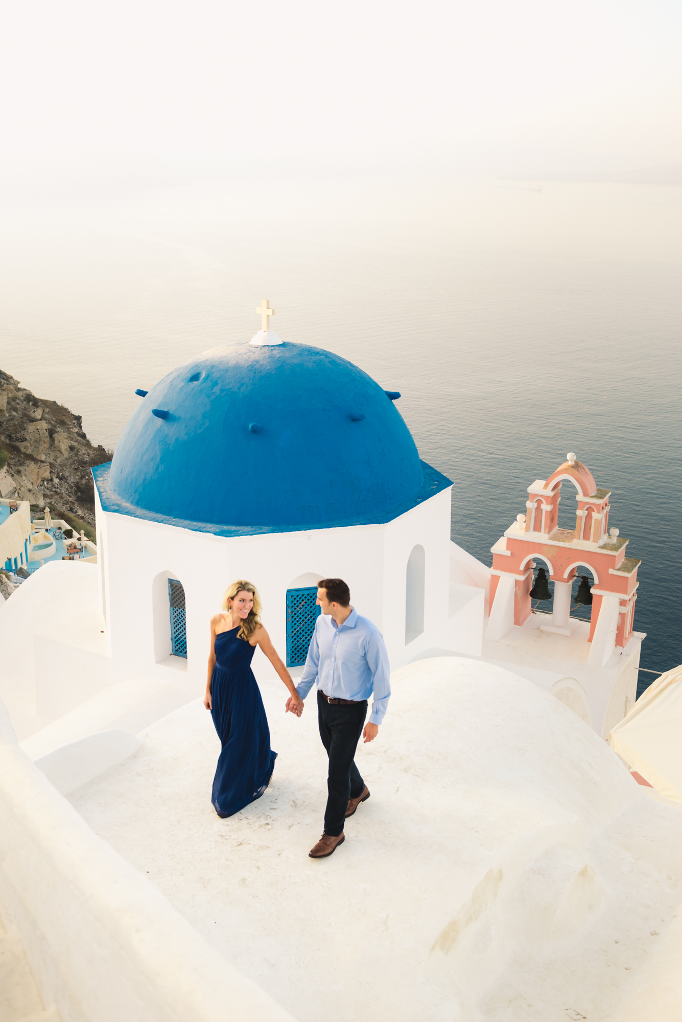 couple walking and smiling o a rooftop in Santorini