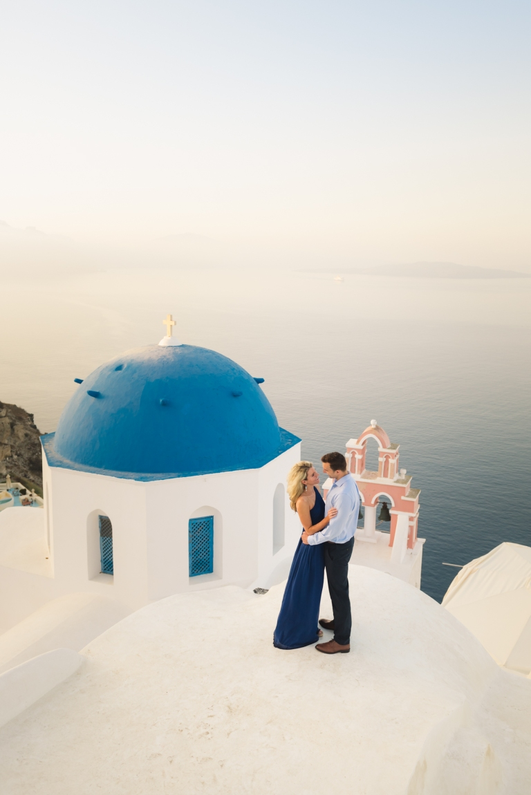 Couple on the rooftop, next to the blue domes in Oia