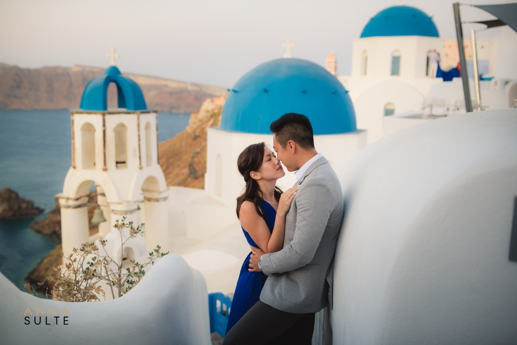 Greece photoshoot. Blue churches and a couple hugging.