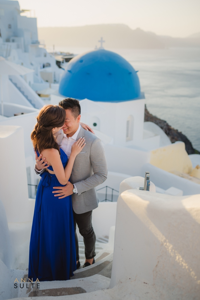 Couple standing in front of blue dome, Santorini.
