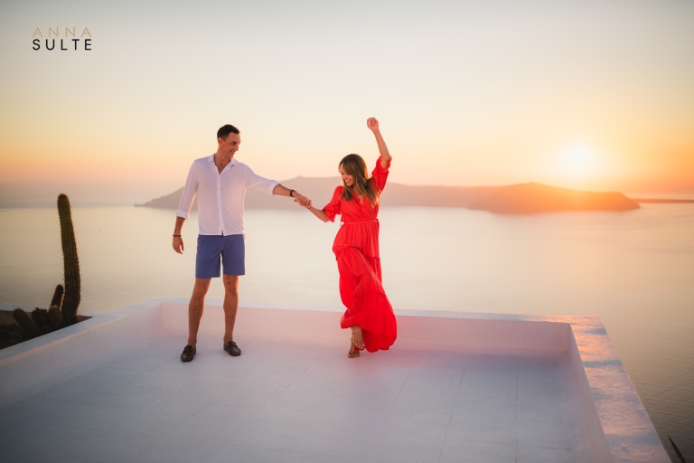 Dancing on the rooftops of Santorini at sunset. Pre-wedding photo shoot in Greece.
